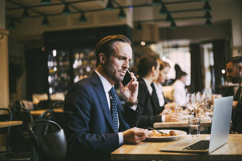 Male business person talking on phone while eating food in restaurant - MASF20065