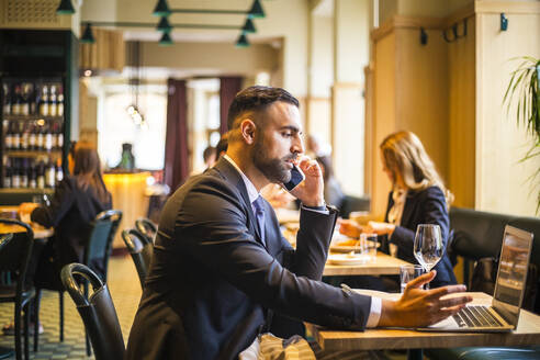 Side view of businessman talking on phone while using laptop in restaurant - MASF20068