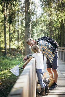 Father with backpack talking to daughter on footbridge in forest - MASF20192