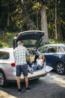 Rear view of father standing with picnic basket while daughter sitting in car trunk - MASF20207