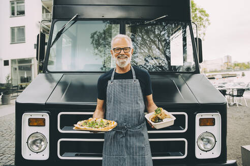 Portrait of smiling owner with food plate standing against commercial land vehicle - MASF20234