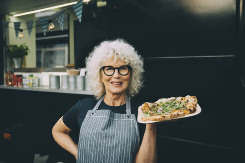 Portrait of senior owner with street food against commercial land vehicle in city - MASF20240