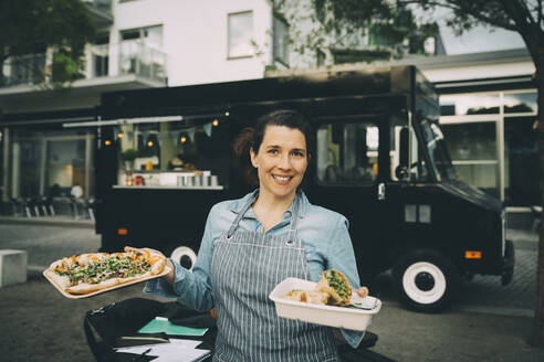 Portrait of smiling female owner with indian street food against commercial land vehicle - MASF20243