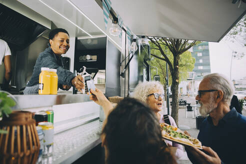 Smiling owner giving credit card reader to customer for payment while standing in food truck - MASF20261