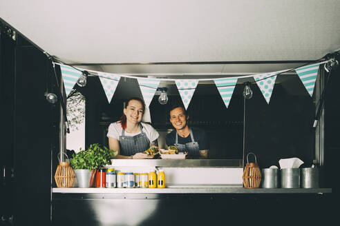 Smiling female owner and assistant standing in food truck - MASF20279