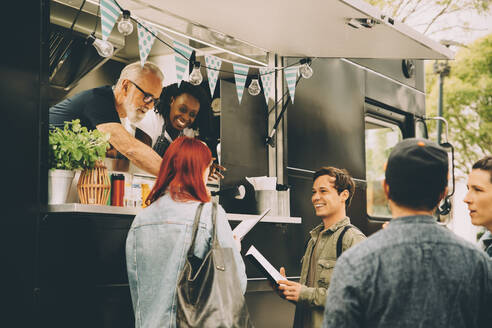 Owner with assistant talking to smiling customers by food truck - MASF20294