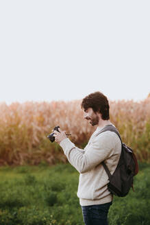 Mid adult man with backpack holding camera while standing at field - EBBF01039