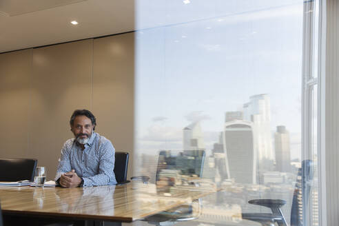 Portrait confident businessman in highrise conference room, London, UK - CAIF29711