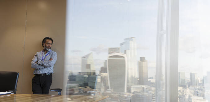 Thoughtful businessman in highrise urban conference room - CAIF29714