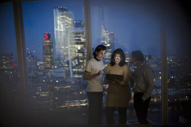 Business people with digital tablet working late at highrise window - CAIF29717