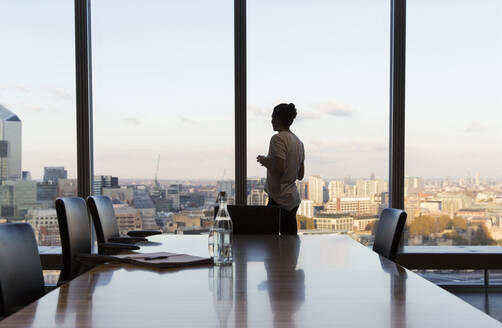 Thoughtful businesswoman at urban highrise office window - CAIF29726