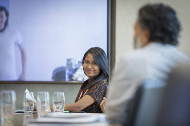 Portrait smiling businesswoman in video conference meeting - CAIF29762
