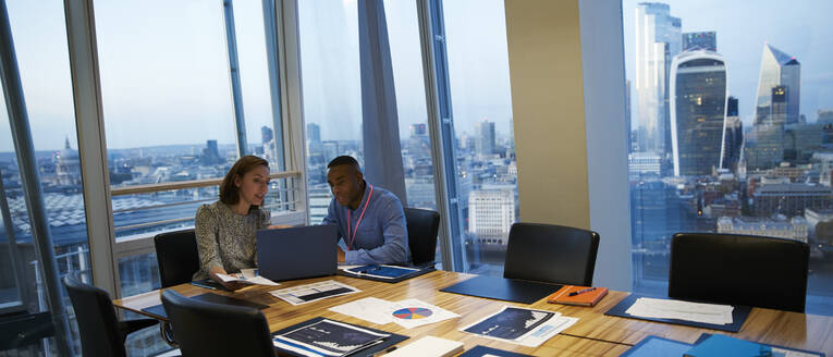 Business people working at laptop in highrise conference room meeting - CAIF29765