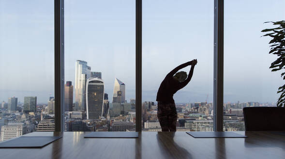 Businesswoman stretching at highrise office window, London, UK - CAIF29792