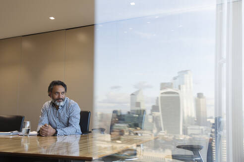 Thoughtful businessman in highrise conference room, London, UK - CAIF29795