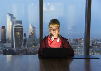 Businesswoman working late at laptop in highrise office, London, UK - CAIF29804
