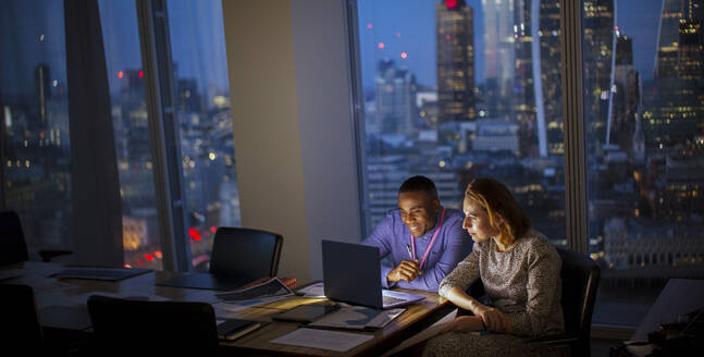 Business people working late at laptop in highrise office, London, UK - CAIF29816