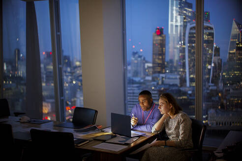 Business people working late at laptop in highrise office, London, UK - CAIF29819