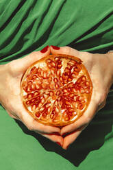 Hands of woman holding halved pomegranate - ERRF04650