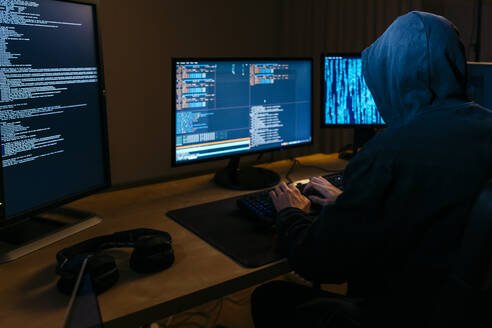 Hacker wearing hoodie working on computer while sitting at office - JRFF04779