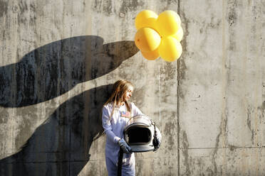 Girl holding balloon while standing against wall on sunny day - GGGF00001