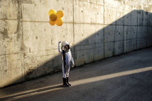 Little girl wearing space helmet holding balloon standing on street against wall - GGGF00004
