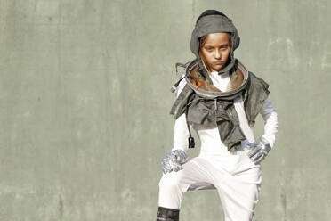 Girl with hand on hip wearing space suit standing against wall during sunny day - GGGF00007