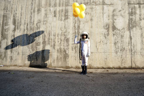 Girl wearing space suit holding yellow balloon standing against wall during sunny day - GGGF00010