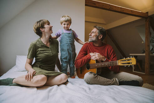 Son standing in between mother and father playing guitar sitting at home in bedroom - MFF06624
