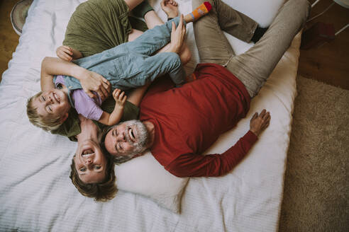 Mother, father and son lying on bed at home - MFF06630