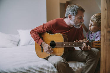 Father playing guitar in front of son while sitting on bed at home - MFF06642