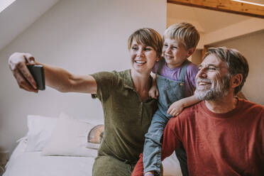 Happy mother taking selfie on smart phone while father and son sitting beside at home - MFF06648