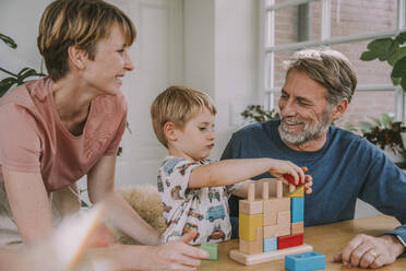 Mother and father playing with son toy block puzzle at home - MFF06654