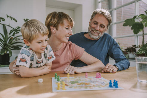 Parents playing board game with son looking away at home - MFF06657