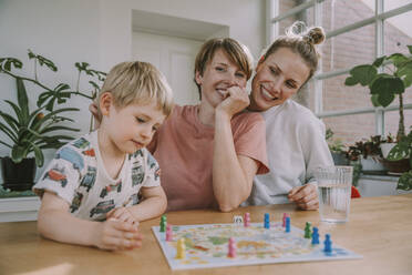 Mothers watching while son playing board game at home - MFF06660