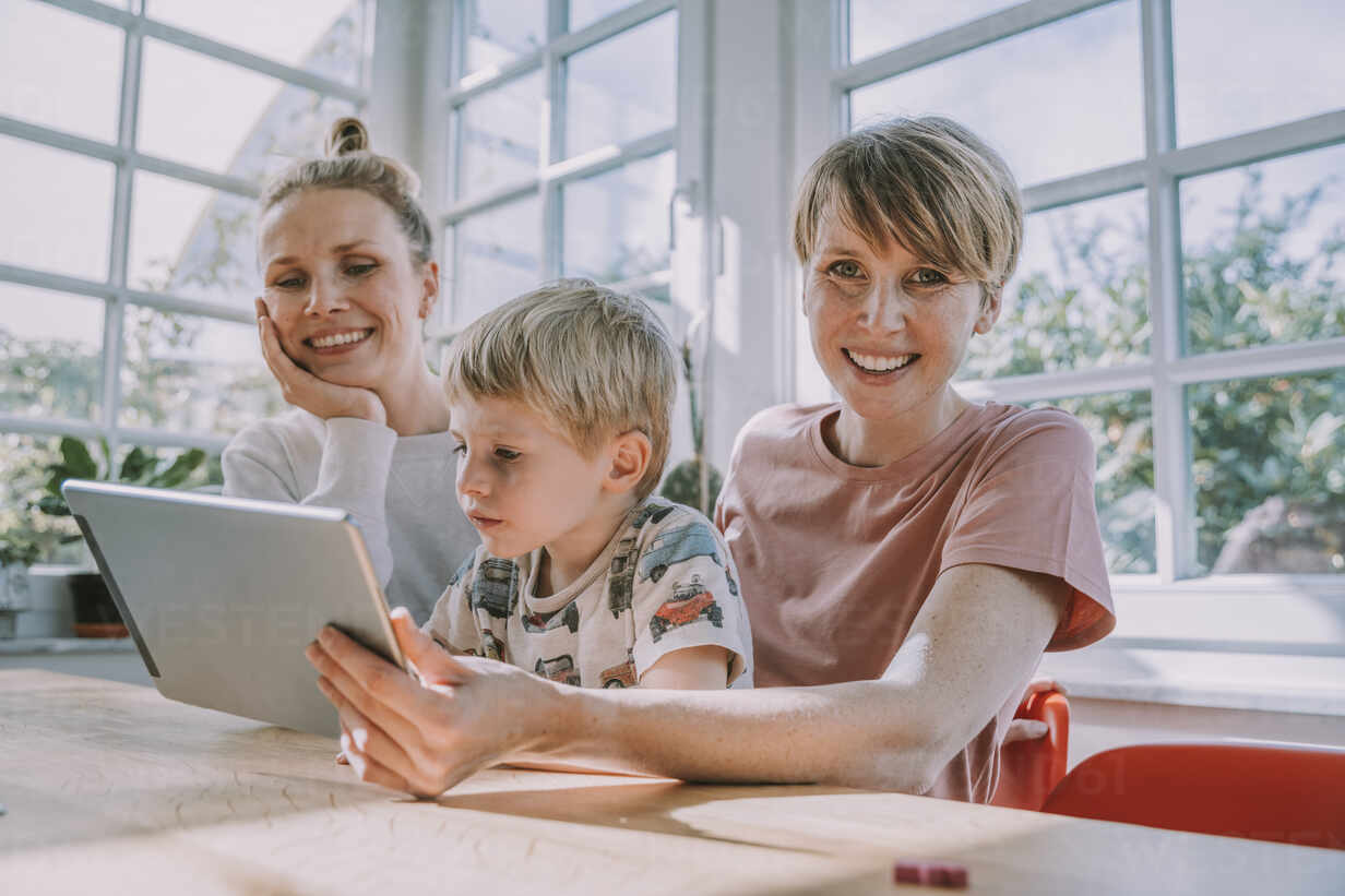 Happy mothers using digital tablet with son while sitting at home - MFF06666 - Mareen Fischinger/Westend61