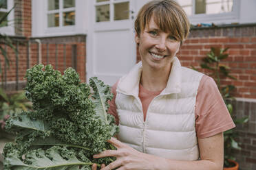 Smiling mid adult woman holding kale leaf while standing in back yard - MFF06669