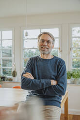 Smiling mature man with arms crossed standing at home - MFF06687