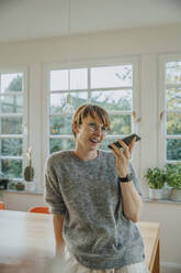 Smiling woman sending voicemail through smart phone while standing at home - MFF06690