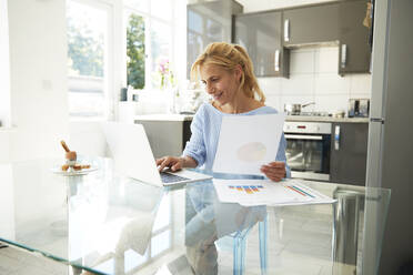 Mature woman working on laptop while sitting in kitchen at home - PMF01422