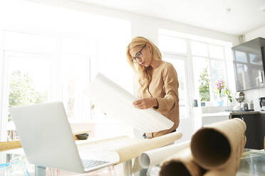 Mature woman holding map working on laptop while standing at home - PMF01437
