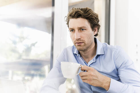 Mid adult man drinking coffee while sitting in office - UUF21890