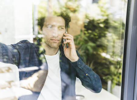 Mid adult man talking on smart phone while looking through window at home - UUF21908