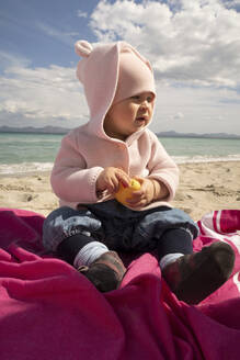 Baby girl sitting on sand at beach during sunny day - SKF01593