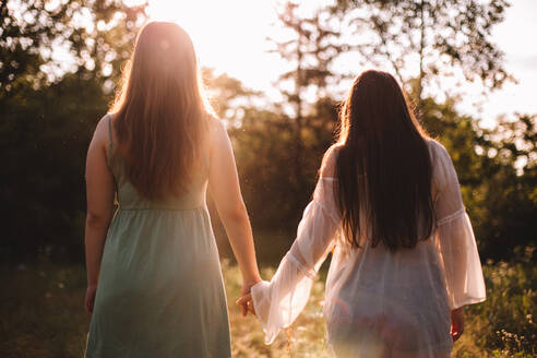 Back view of lesbian couple holding hands while standing in forest - CAVF89834
