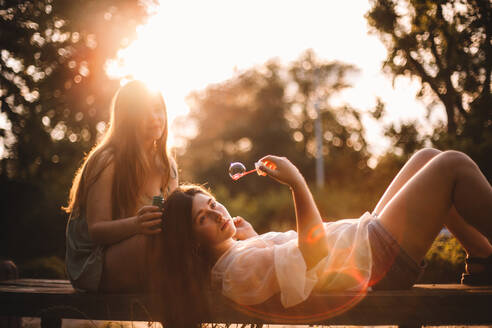 Girlfriends playing with bubbles while relaxing in park in summer - CAVF89840