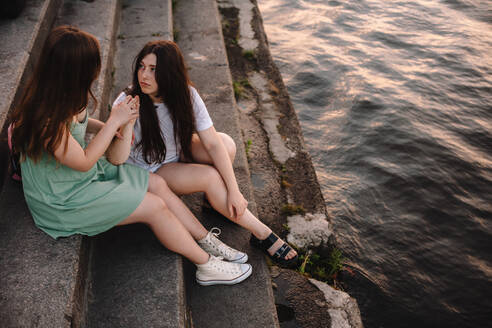 Cute lesbian couple talking while sitting on steps by river in city - CAVF89846
