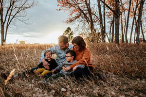 Smiling young family snuggling in a field on a fall evening - CAVF89849
