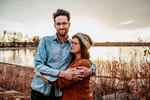 Happy couple hugging near a lake in Denver CO on a autumn evening - CAVF89852