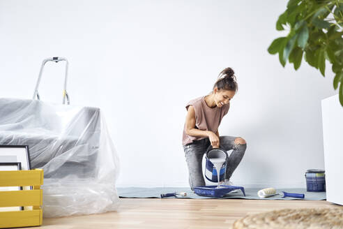 Smiling young woman pouring paint in paint tray while kneeling at home - BSZF01715